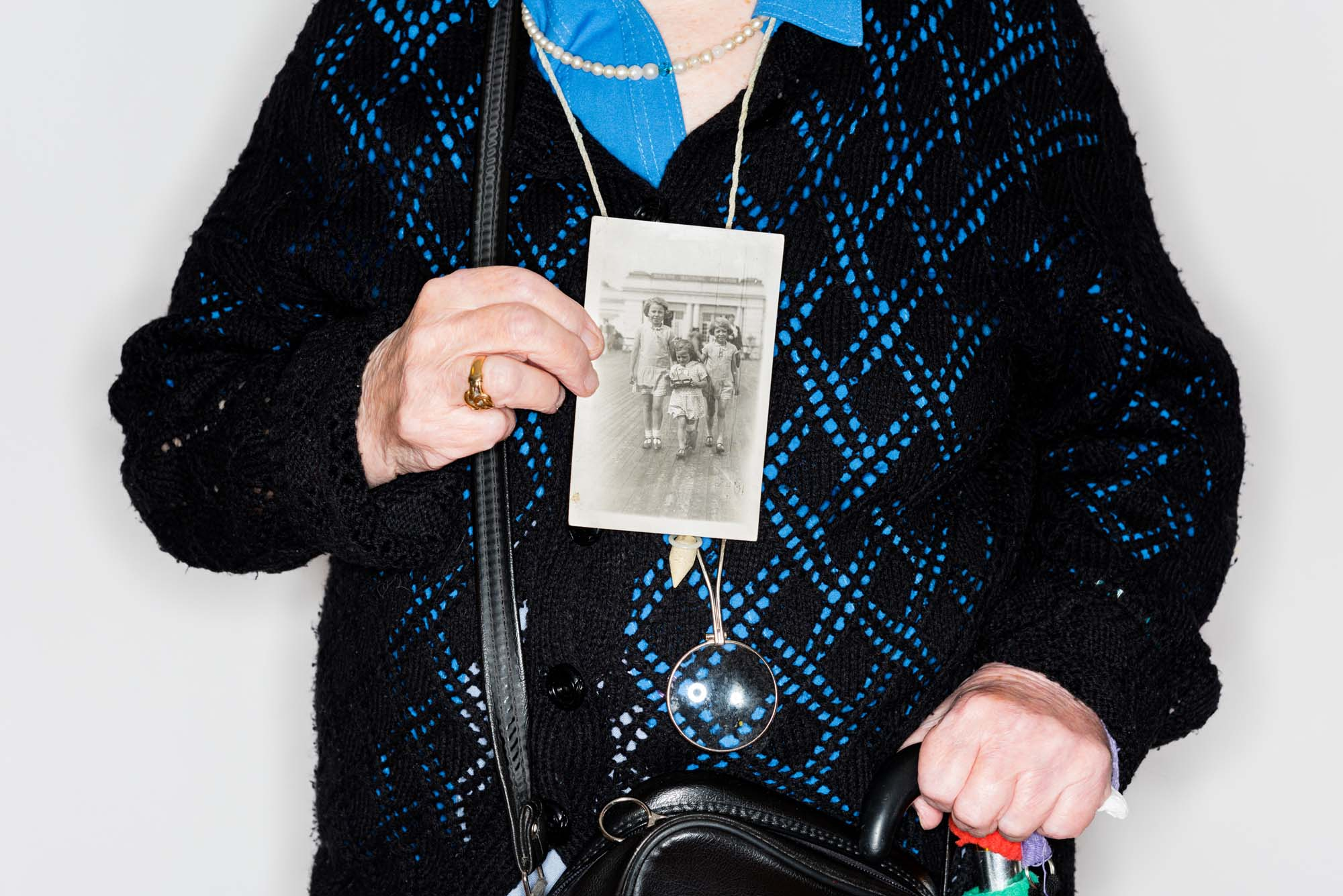 a copped photo of a woman holding up an old black and white photograph