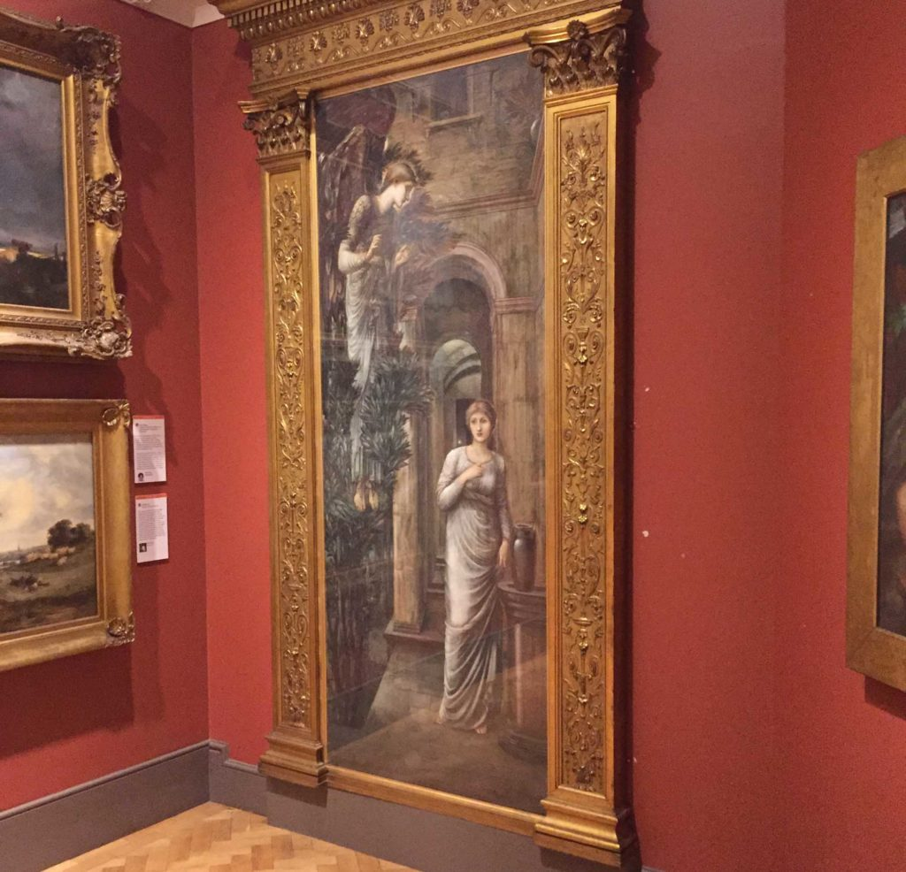 a photo of a gallery with a Burn Jones painting in the corner