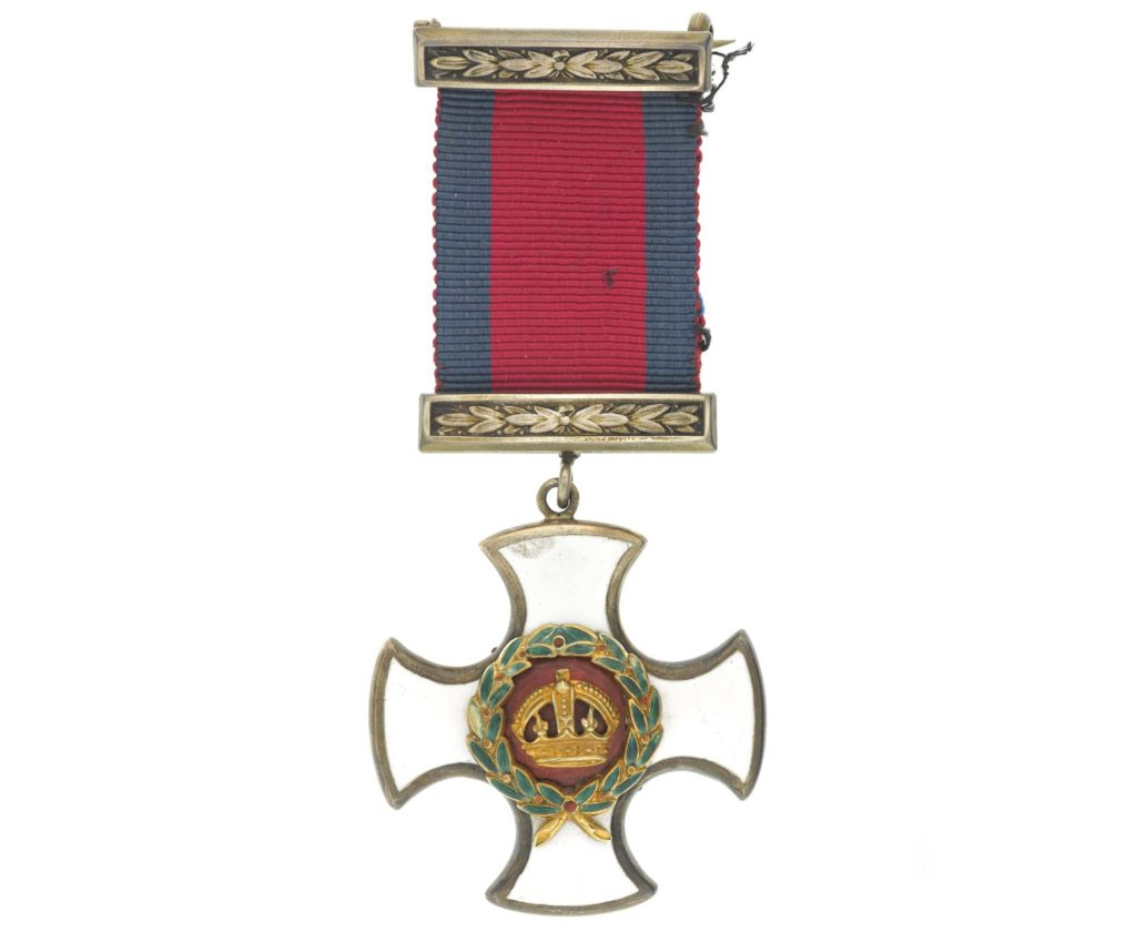 a photo of a medal in the shape of a curved cross with white enamel and kings crown to its centre