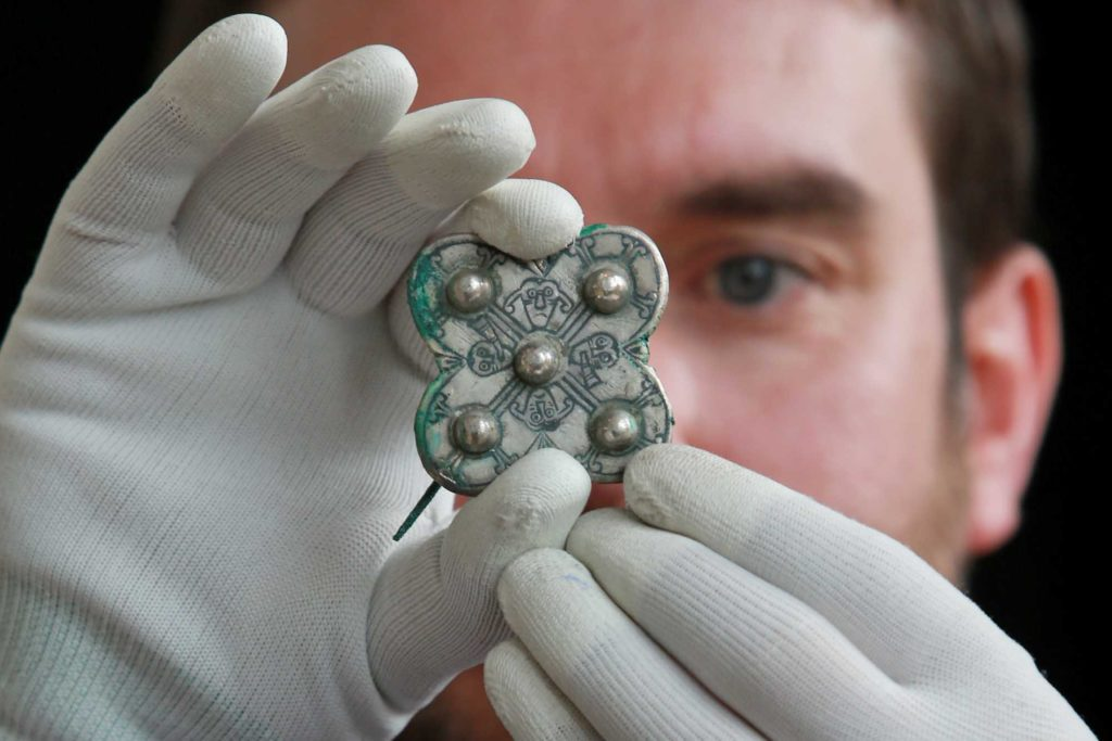 a photo of a man holding a silver coloured brooch