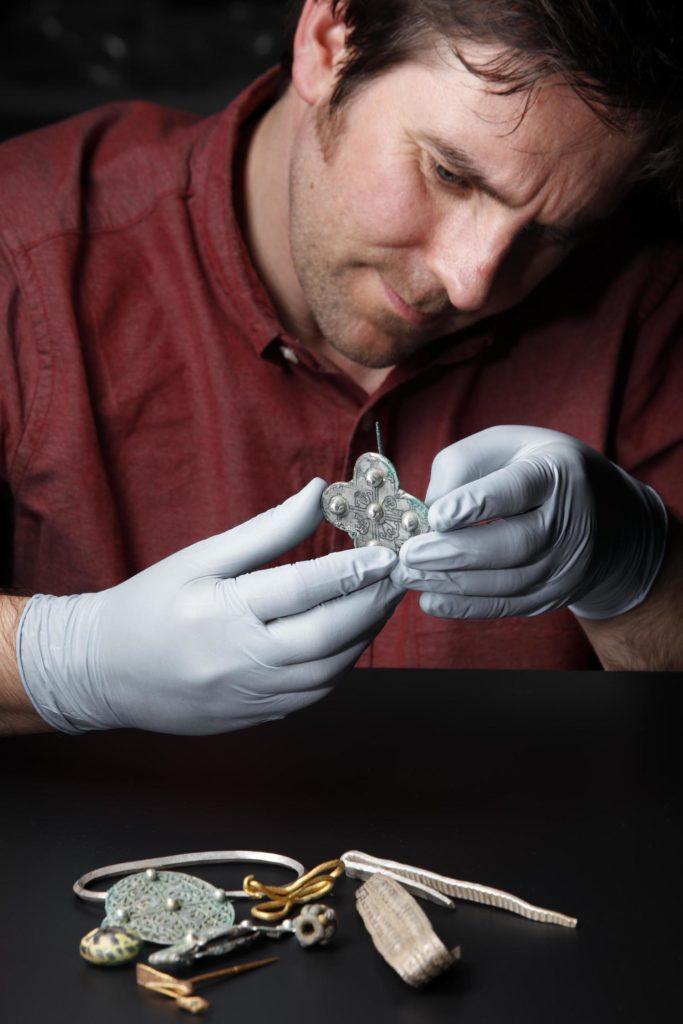 a photo of a man examining a brooch