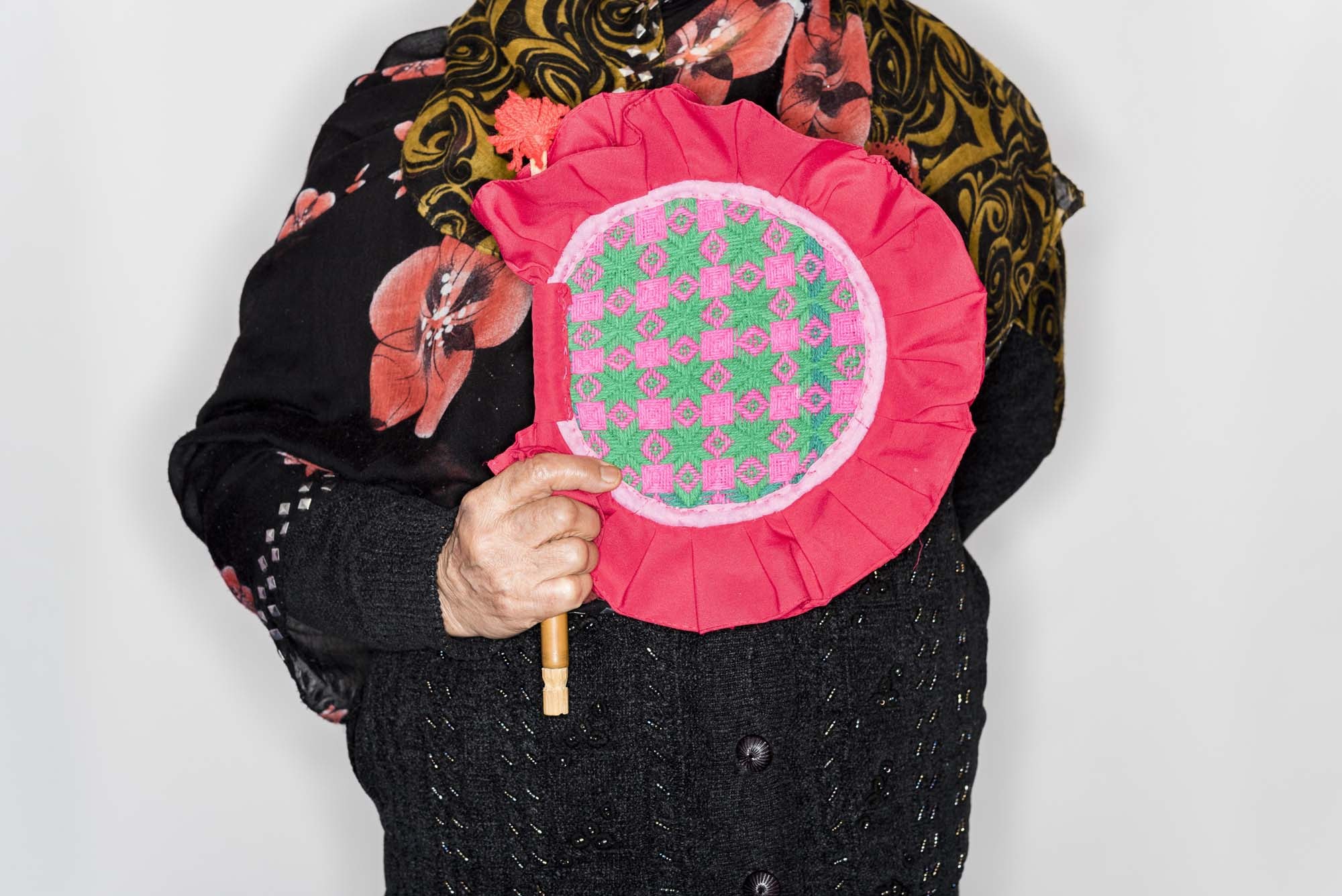 a cropped image of a woman holding a large, round pink fan