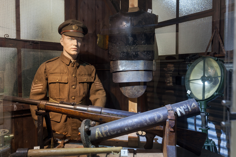 A manequin dressed in a WW1 uniform stands behind a table of weapons from the First World War
