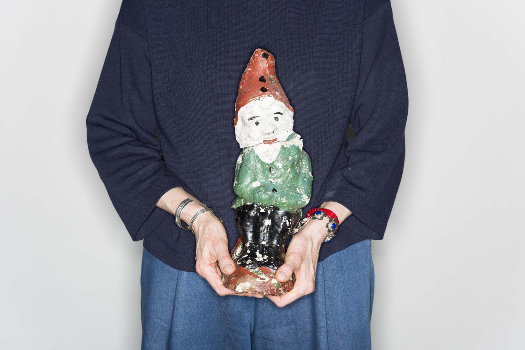 a cropped photo of a person holding a garden gnome