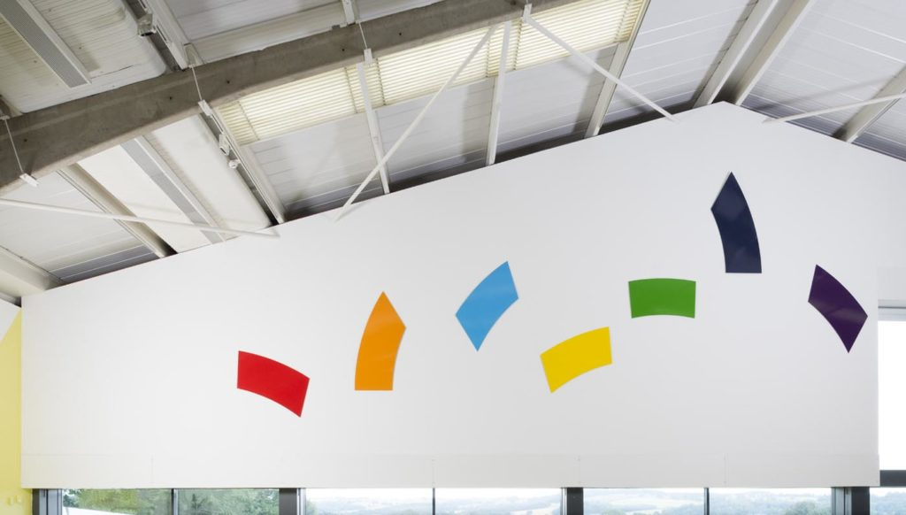 a photo of a series of coloured shapes on a white wall