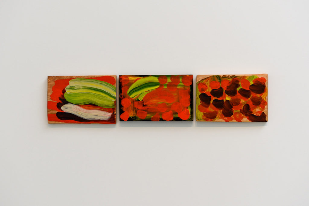 photograph of triptych of orange abstract paintings