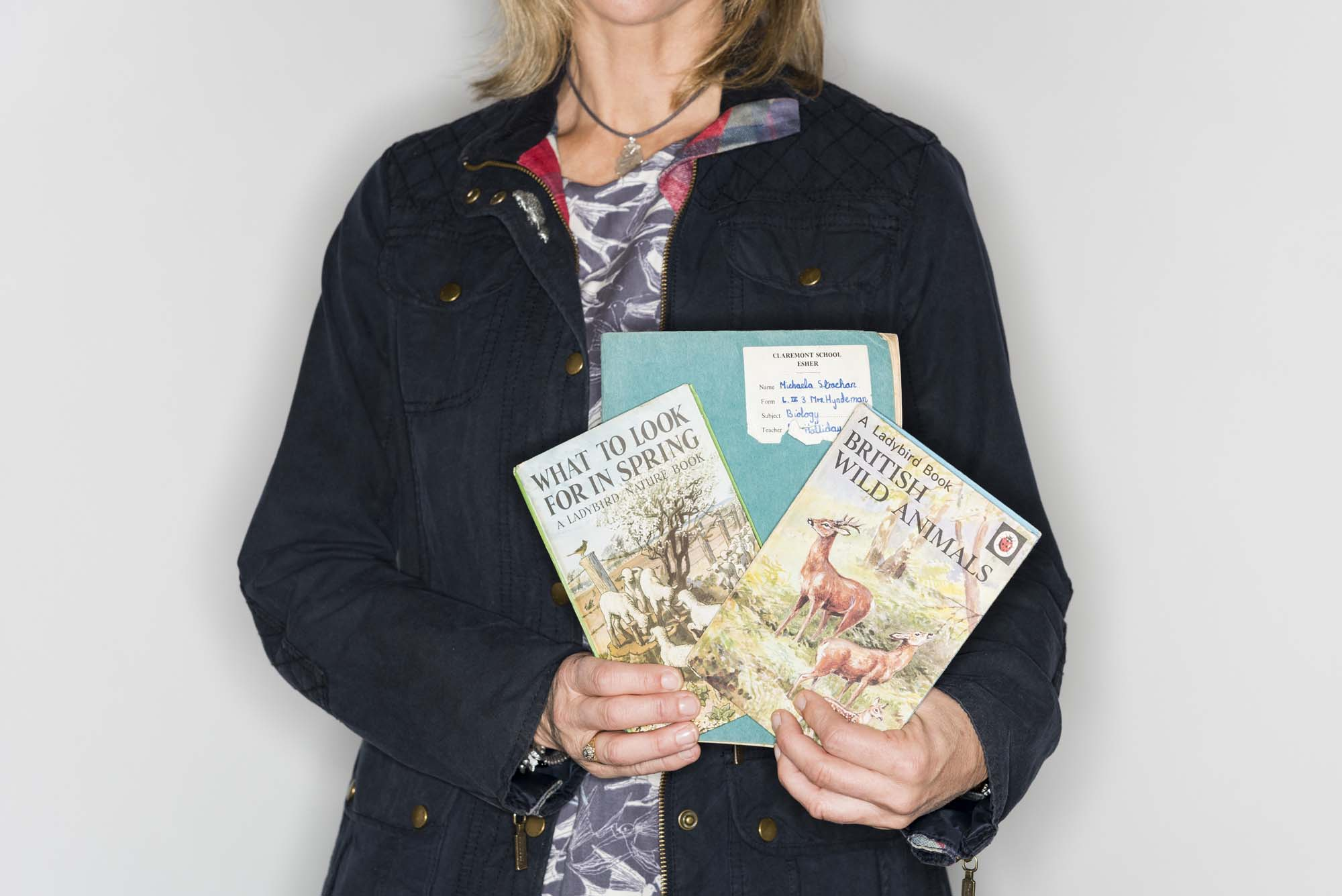 a cropped image of a woman holding two Ladybird books and an exercise book
