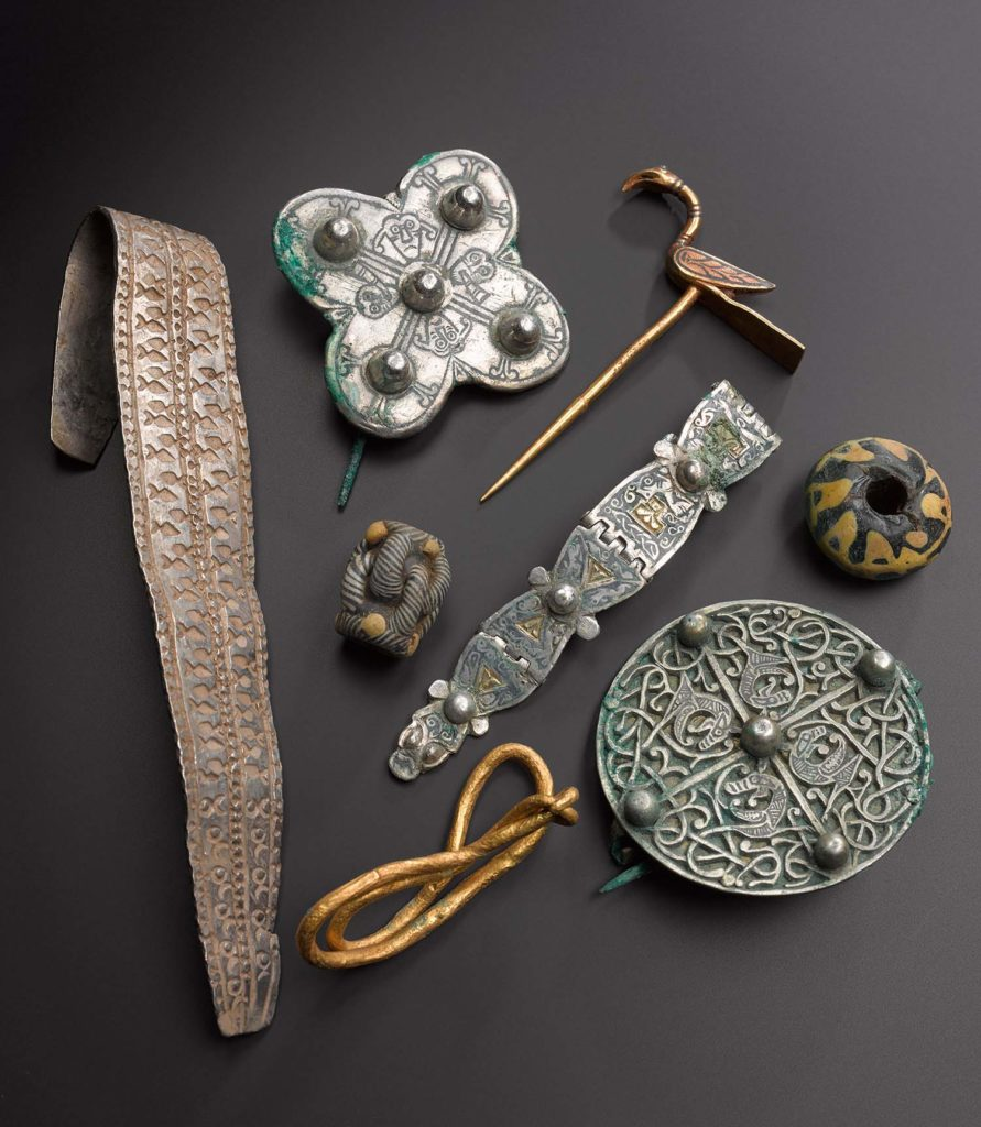 a photo of a range of objects including brooches and wrist bands