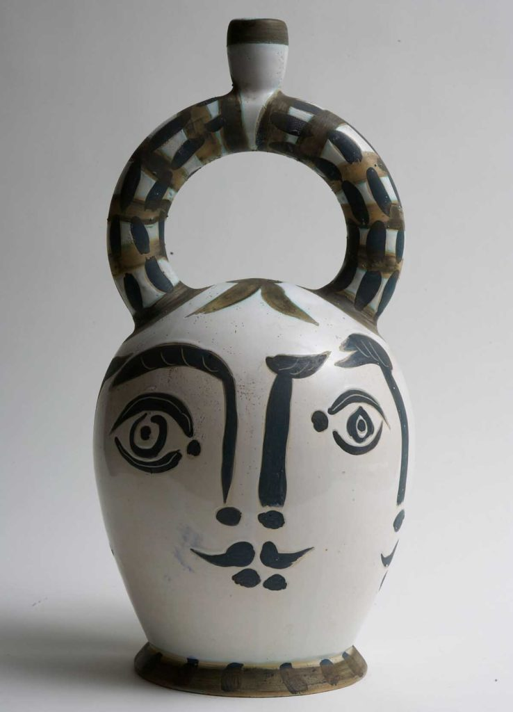 a photo of a Picasso pot with a face on it and circular handle