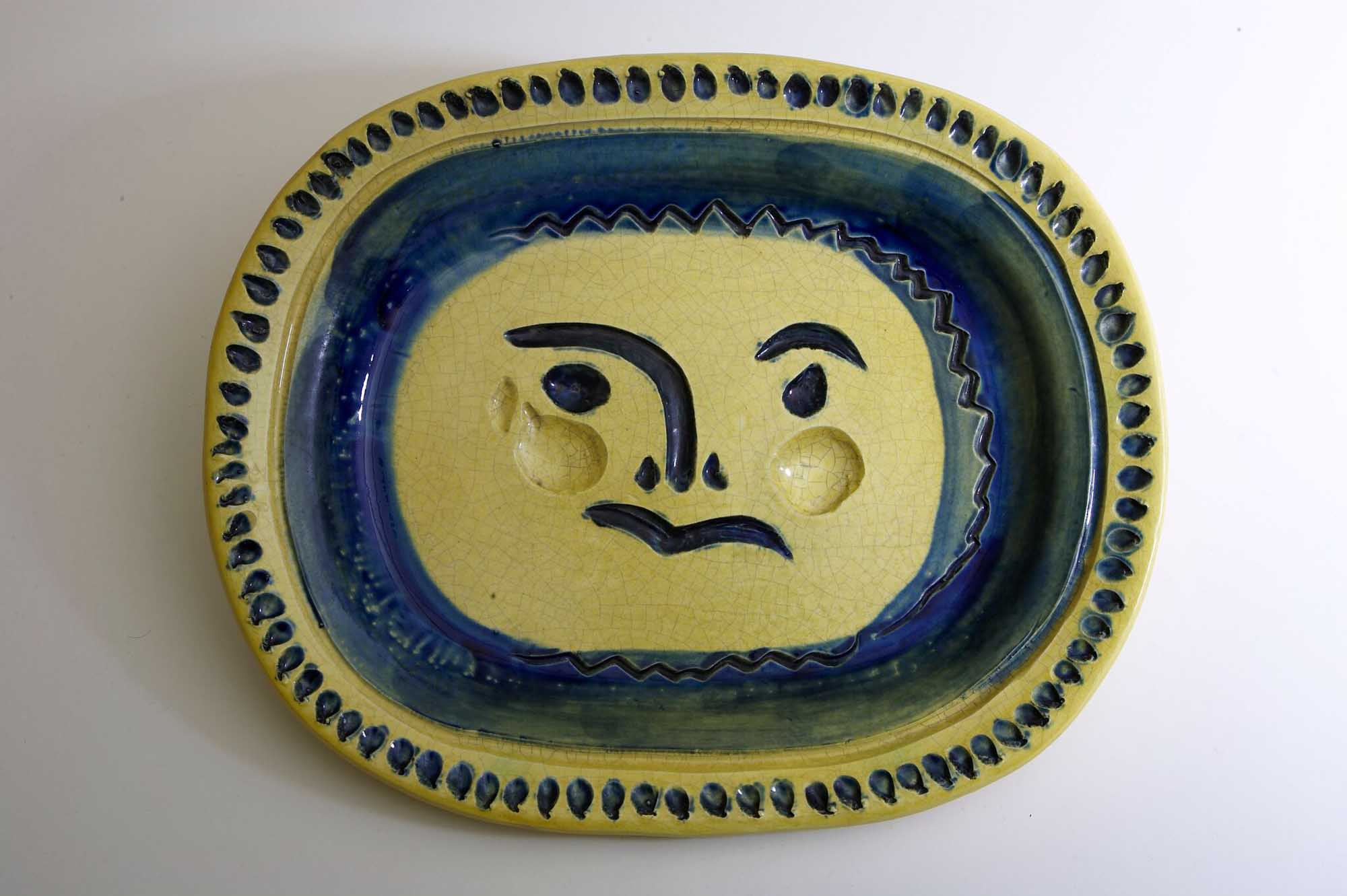 a photo of a yellow and blue dinner plate by Picasso with a face at its centre