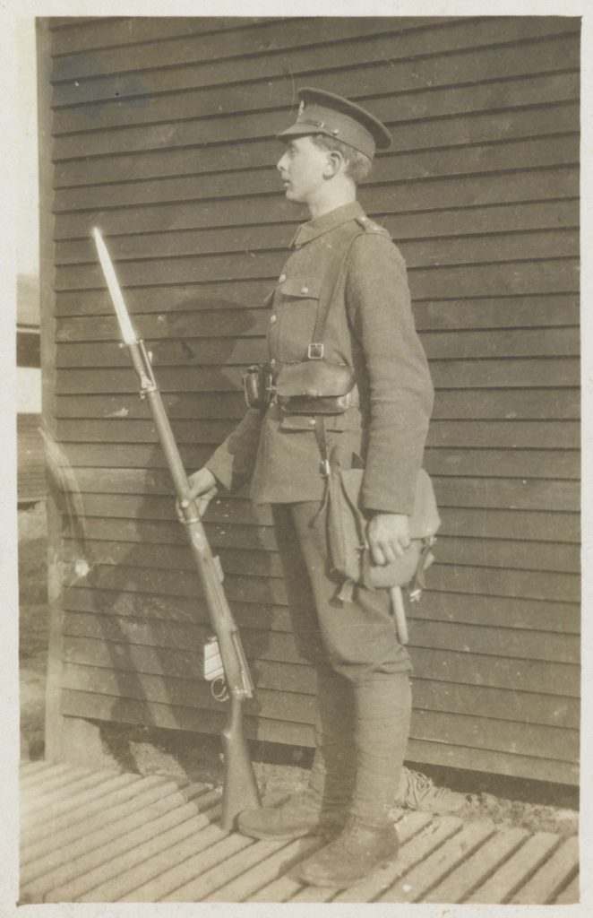 a photo of a soldier in unifrom standing on guard with a rifle and bayonet
