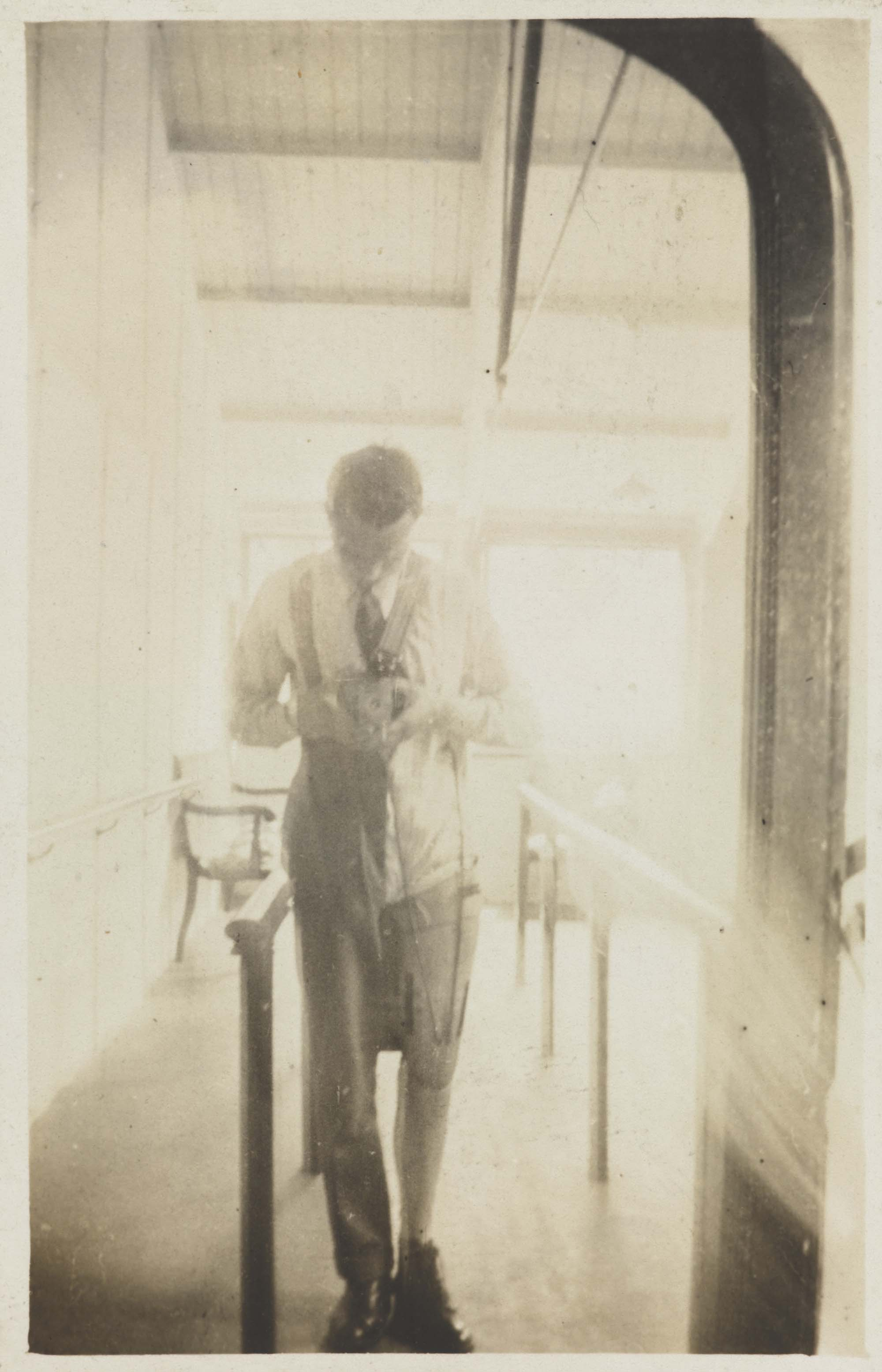 a photo of a man standing either side of parallel bars with a false leg taking a self portrait with a box camera