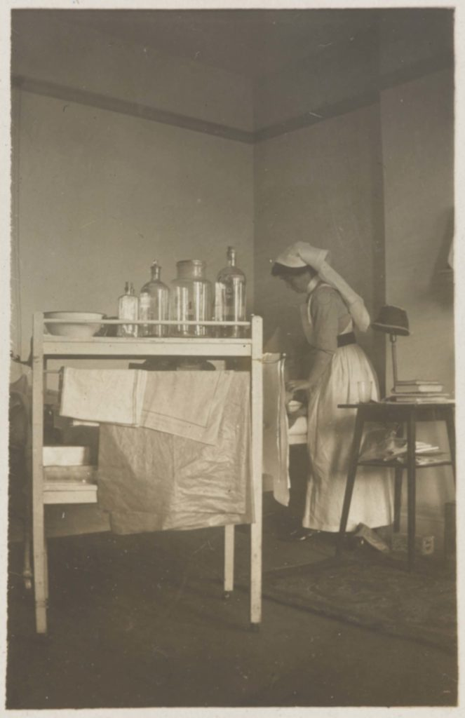 a black and white photo of a nurse on a ward with a tbale with bottle on it in the foreground