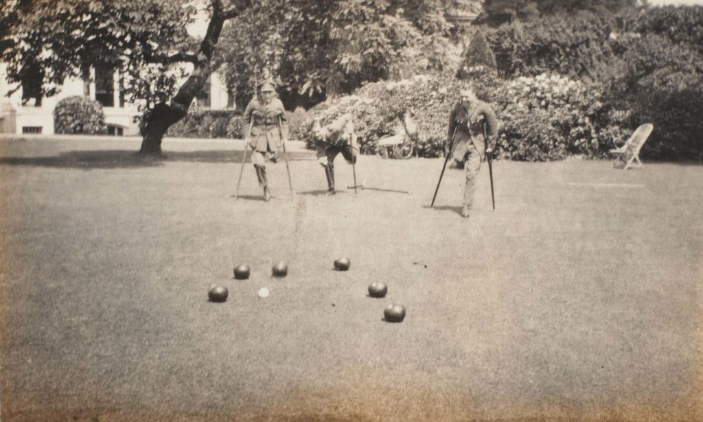 a black and white photo of three men on crutches and one leg smiling as they play bowls