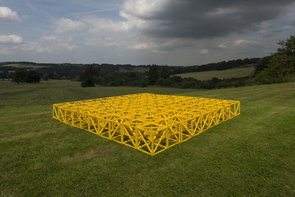 a photo of a yellow sculpturail structure resembling steel roof girders outside in a field