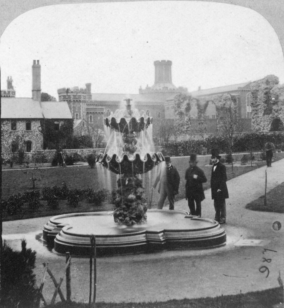 historic photograph of three men in top hats standing by an ornate fountain, a prison can be seen in the background