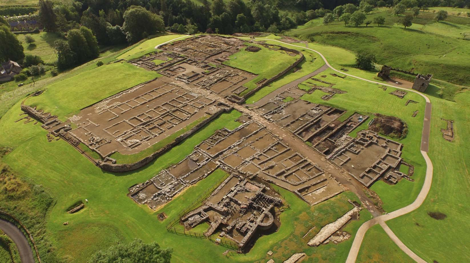 an aerail view of an archaeological site woith foundations and rooms spanning out in a square shape