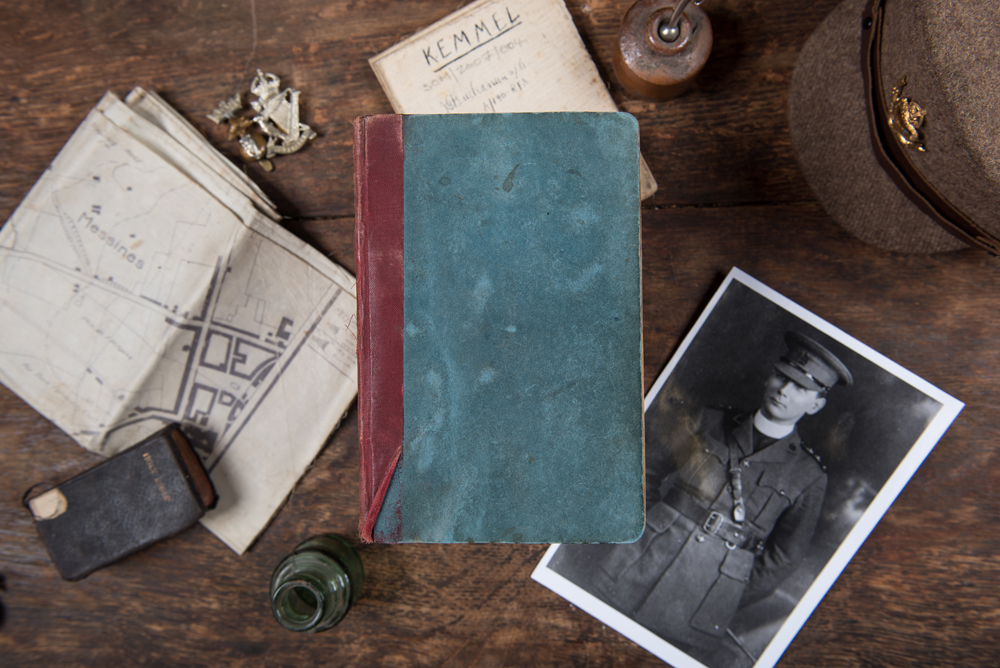 A table with objects from the Battle of Messines 1917, including a book, a photograph of a soldier, a hat and badge and a map.