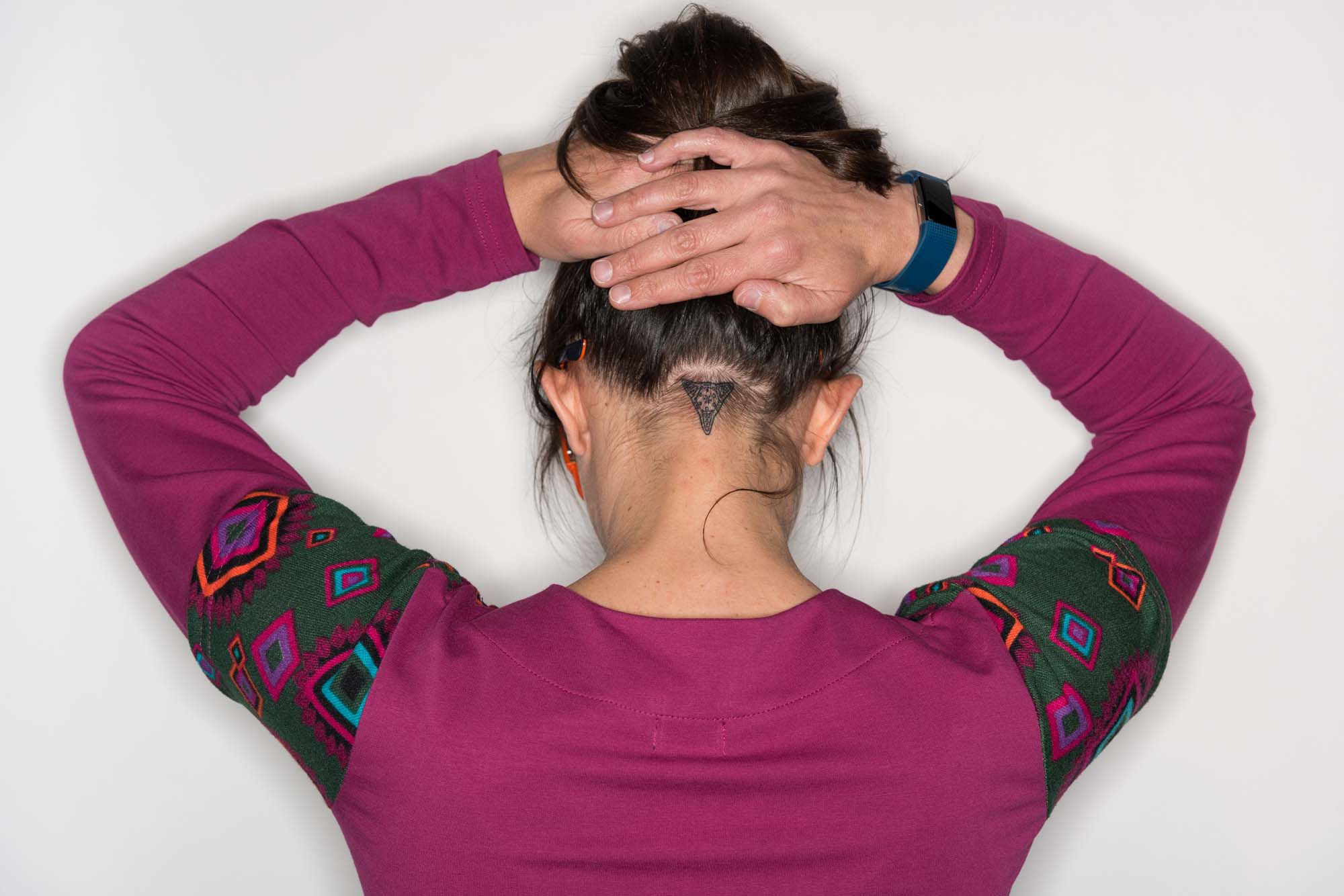 a photo of a woman raising the hair on the nape of her neck to reveal a tattoo