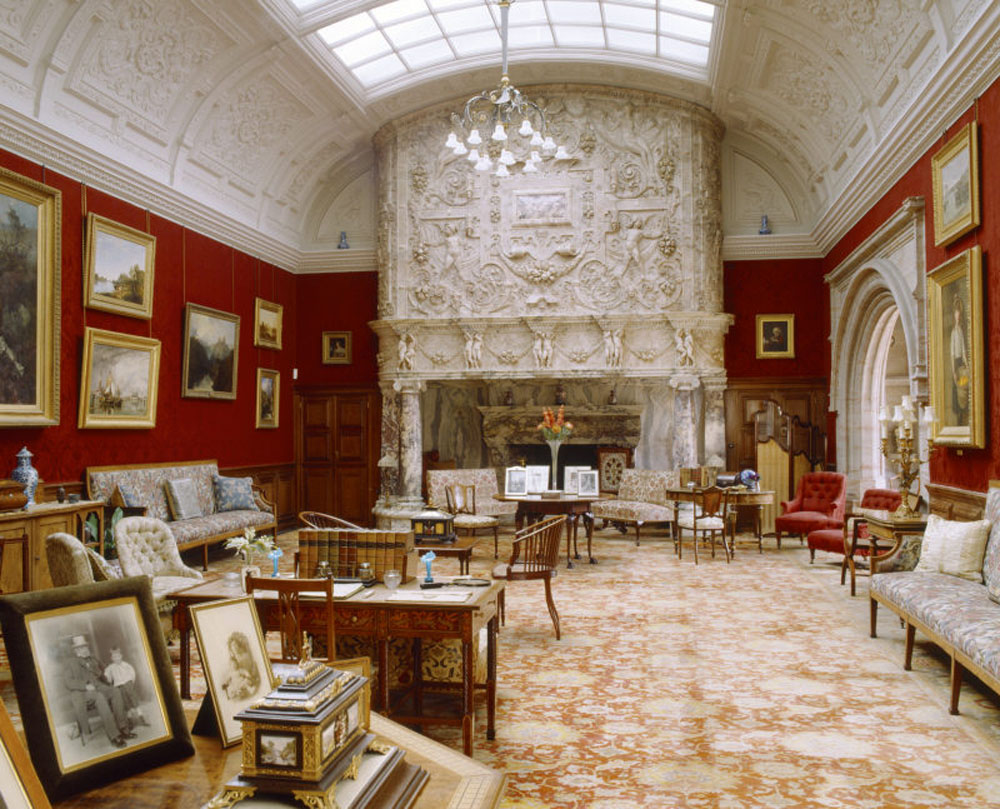 The Drawing room at Cragside, a grand room with red walls and an intricate, white chimneypiece