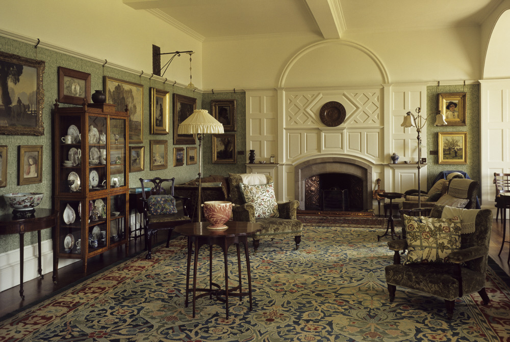 A photograph of the Drawing room at Standen, a large white room with victorian furniture and a floral carpet by William Morris