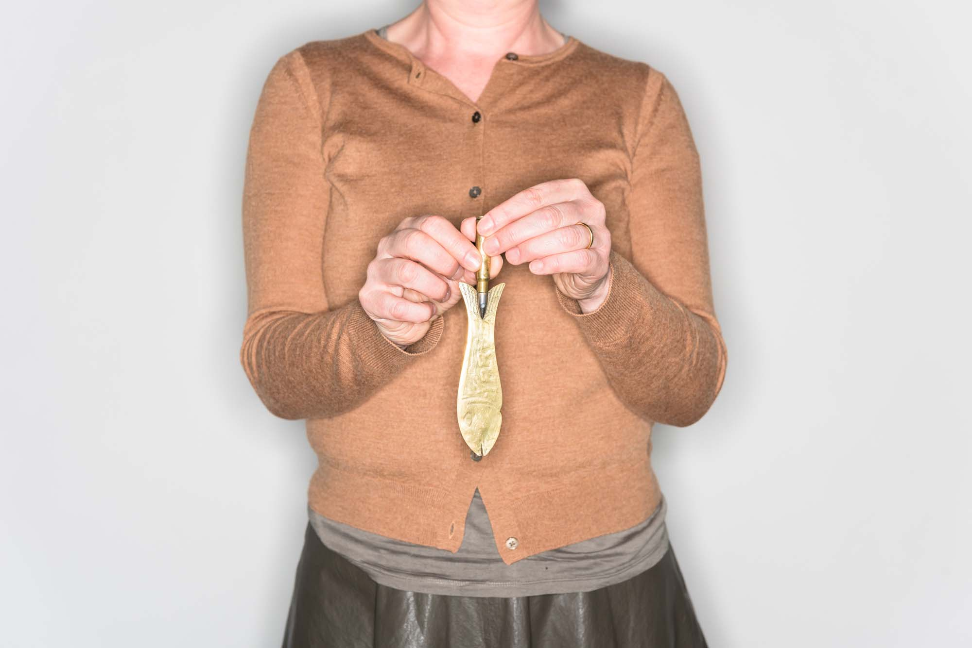 a cropped picture of a woman holding a small brass knife