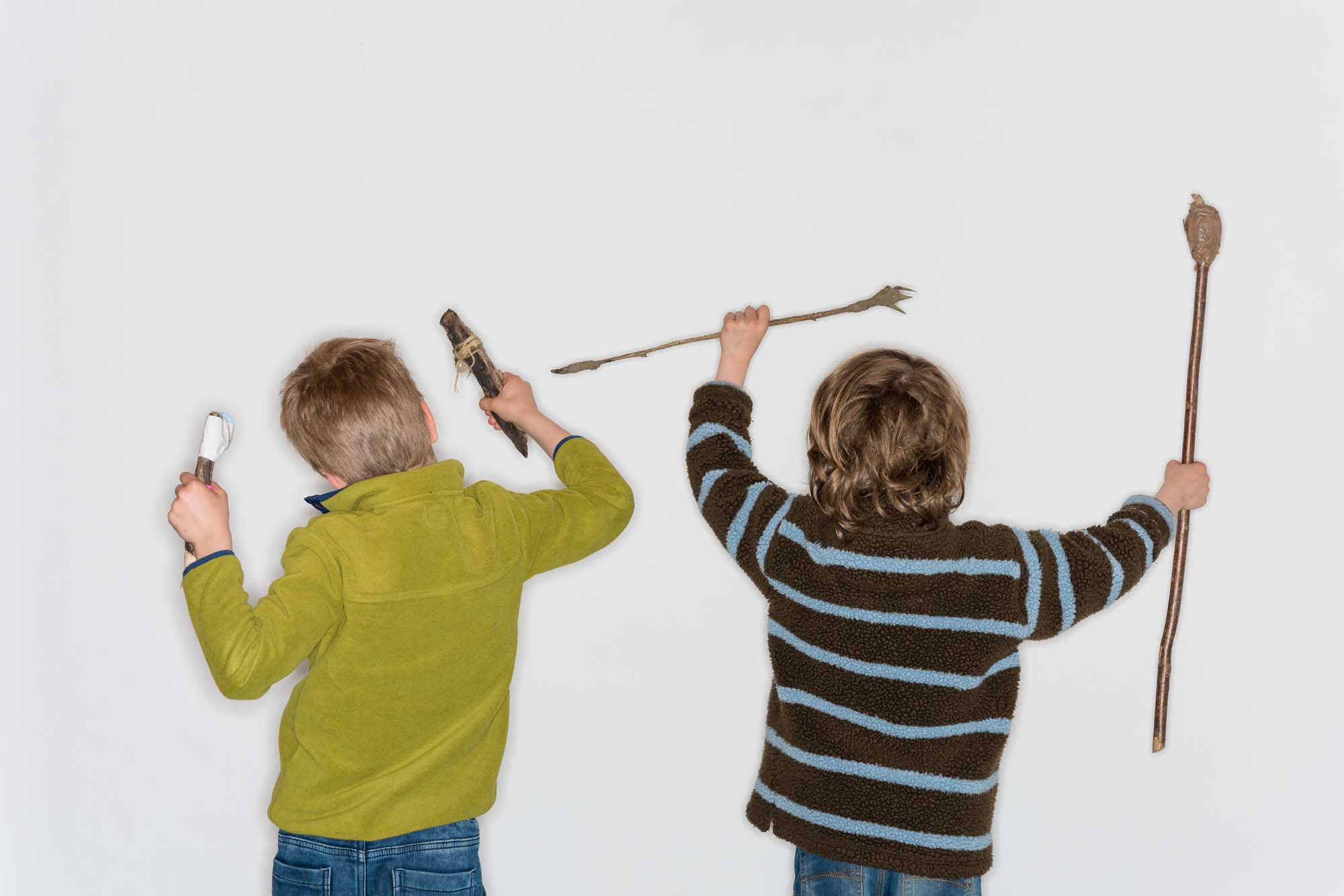 a photo of two kids holding sticks