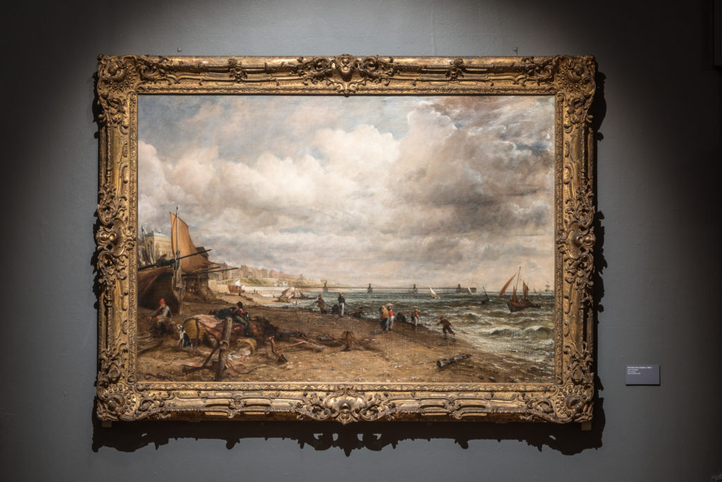 photograph of painting of a seascape in an ornate frame on a grey wall.