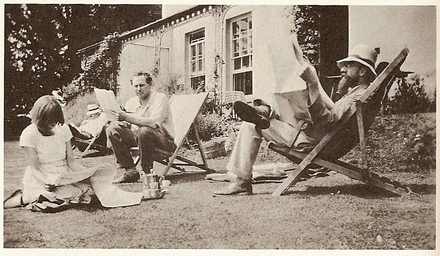 historic photograph showing three men in deck chairs and a woman seated on a lawn outside a large house