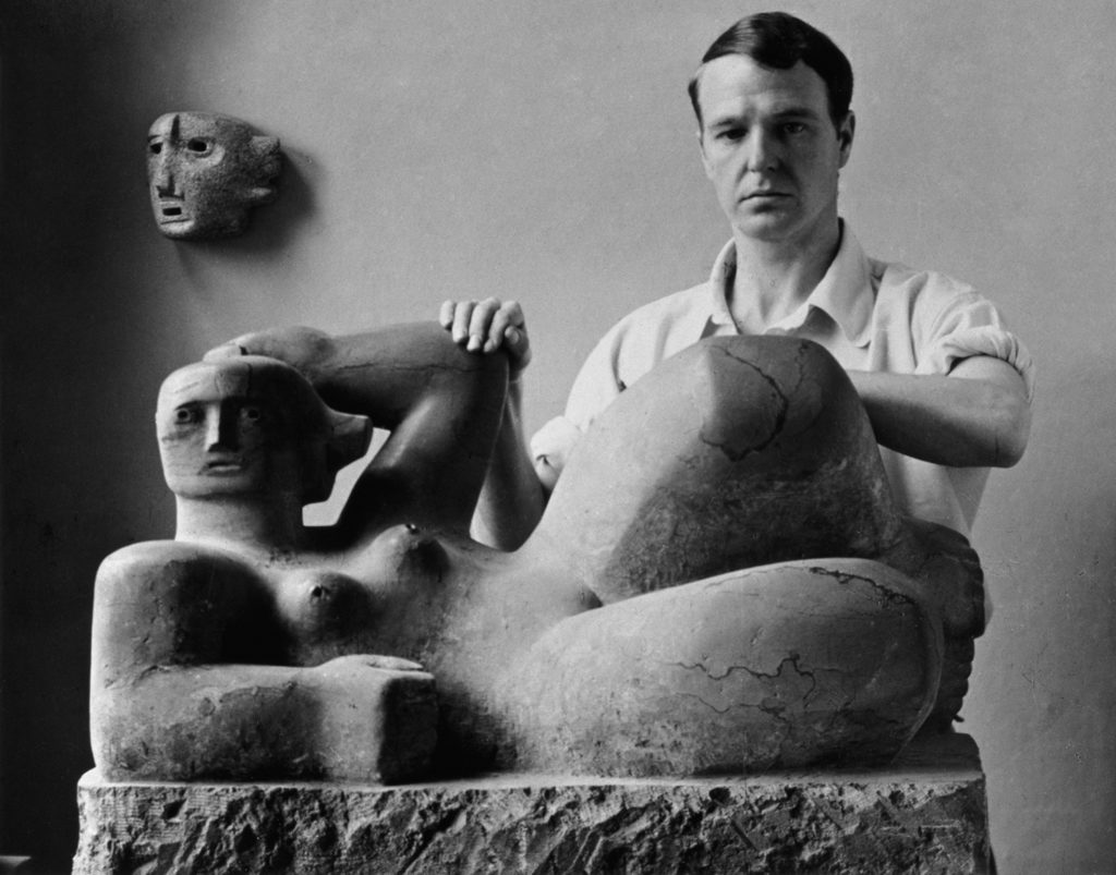 photograph showing henry moore in his studio with two of his sculptures