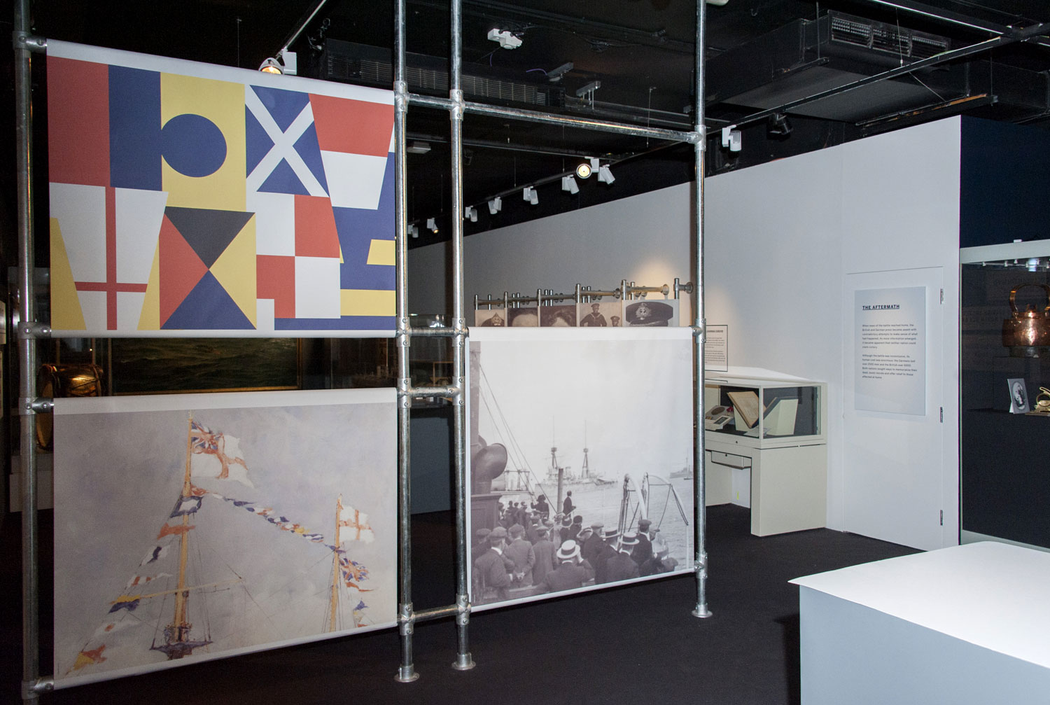 photograph of interior of museum gallery showing naval flags and photographs