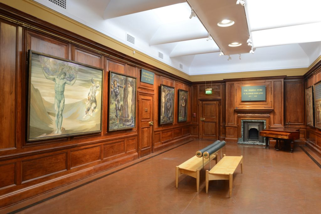 a photo of a woode panlled gallery with Burne-Jones paintings