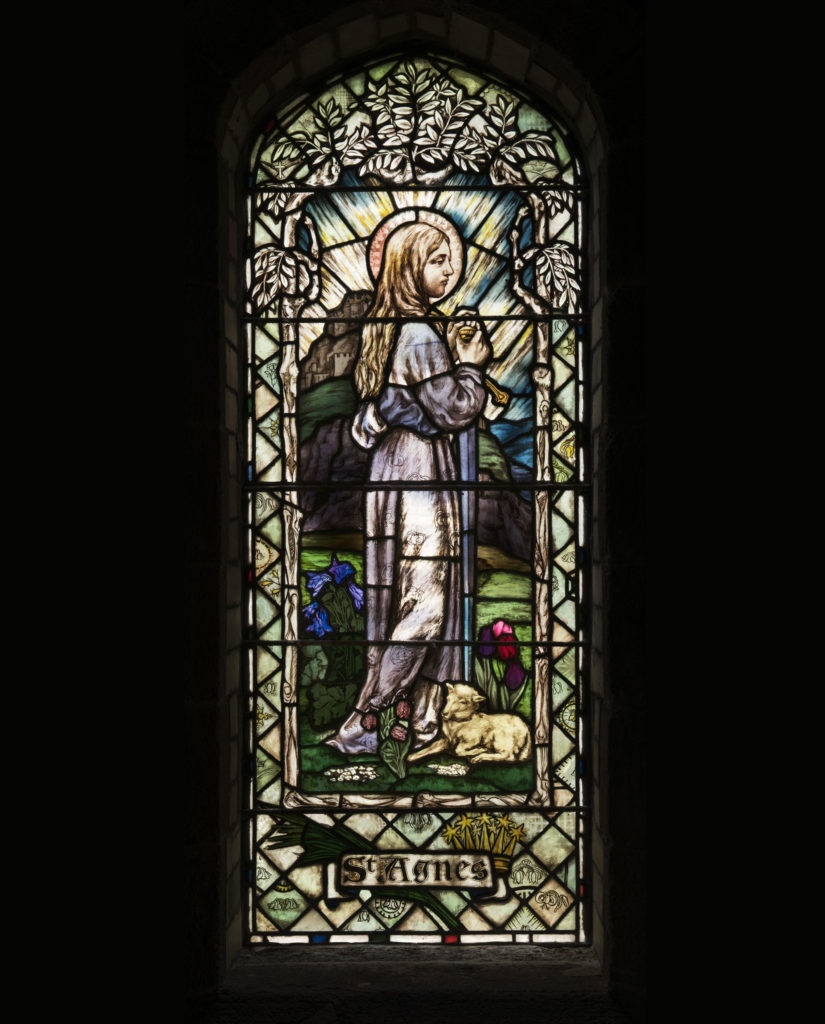 photograph of stained glass window depicting St Agnes holding a sword with a lamb at her feet