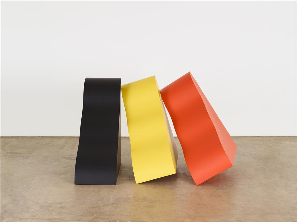 photograph of sculpture consisting of three wedge-shaped wooden blocks leaning to the left in black, yellow and orange