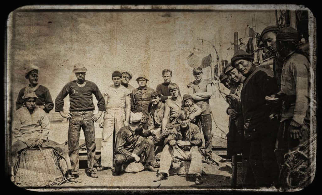 an old photo showing a group of sailors and Chinese workers on a dockside