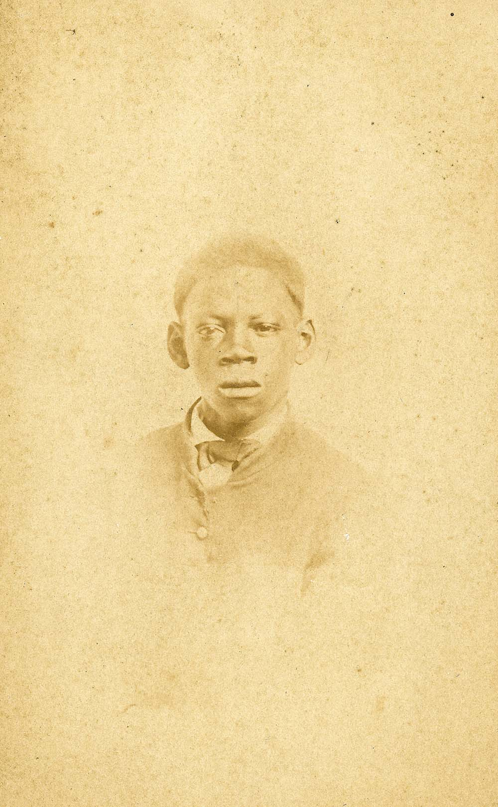 a faded photograph of a young black boy wearing a suit
