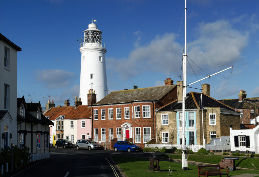 photogrpah of lighthouse in town, behind a row of shops and houses