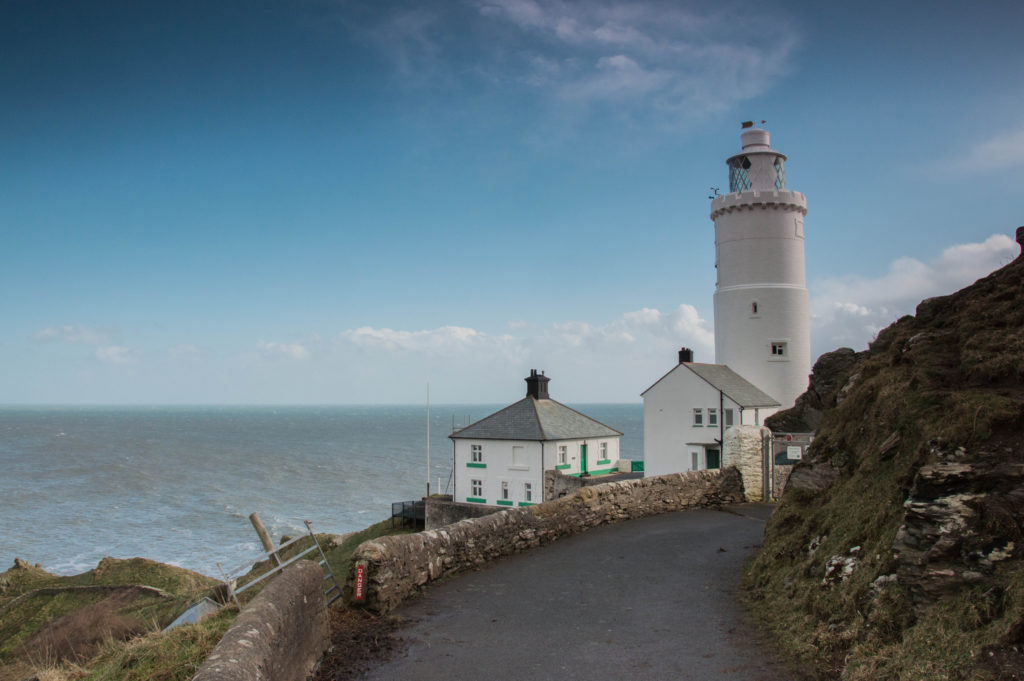 photograph of road leading to white lighthouse, overlooking the sea