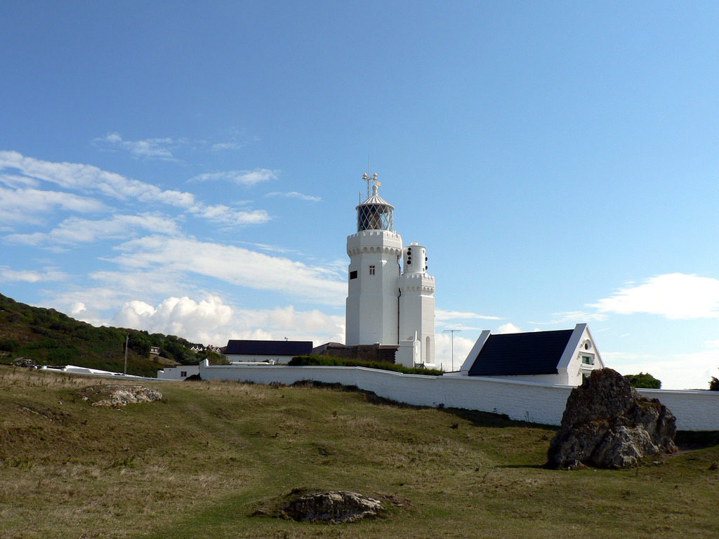 photograph of white painted lighthouse against blue sky with field in foreground