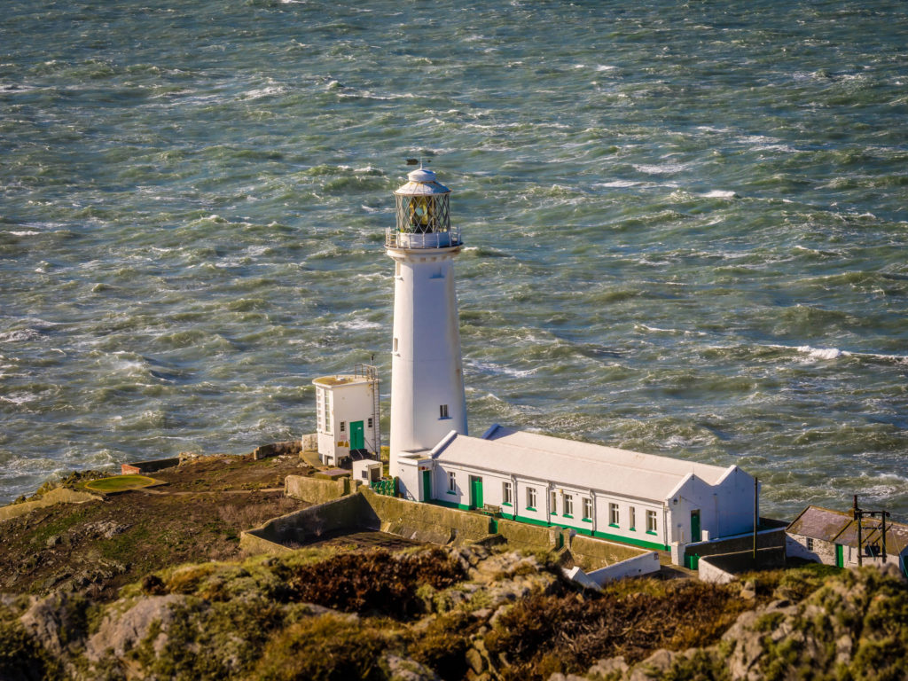 photograph of white lighthouse looking out to sea