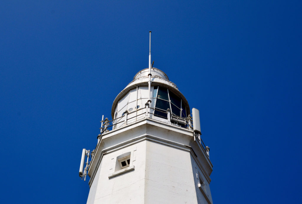 photograph of the top of a white lighthouse against a bright blue sky