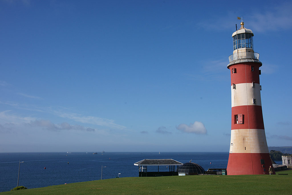 photograph of red and white sriped lighthouse overlooking the sea