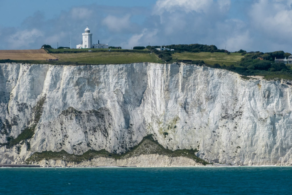 photograph of lighthouse atop the white cliffs over dover from sea