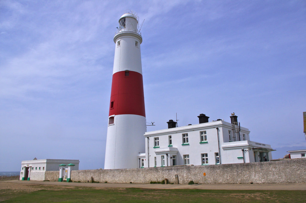 photograph of red and white striped lighthouse with white building to the right