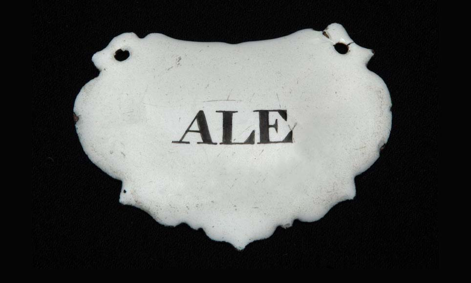 a photo of an enameled token with the word ALE written on it