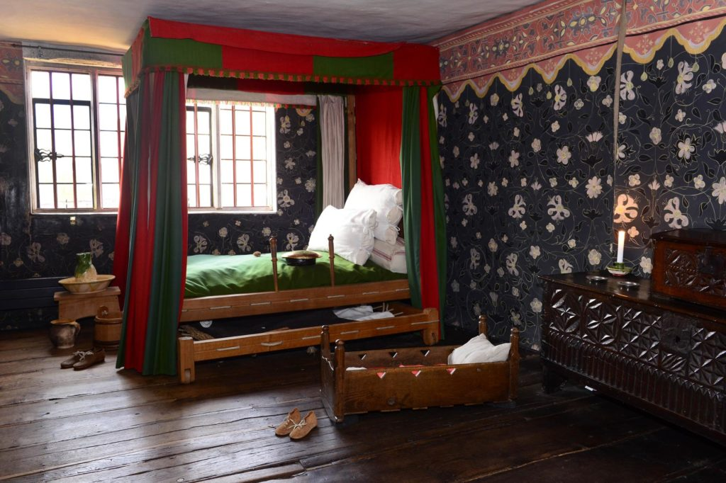 a photo of a an old Elizabethan bedroom with four poster bed on wooden floors