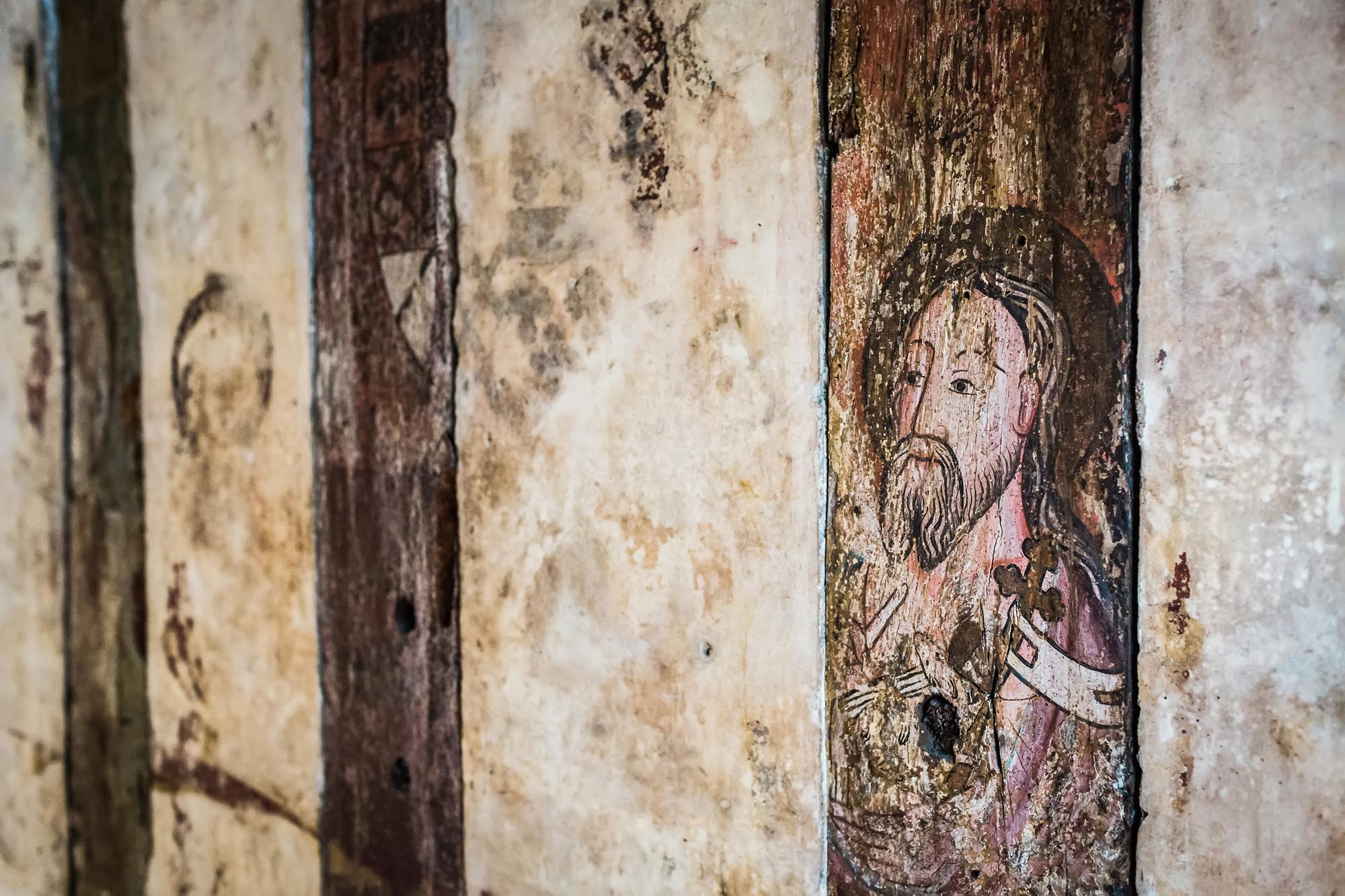 a photo of a painting on wooden beam of the bearded figure of John the Baptist