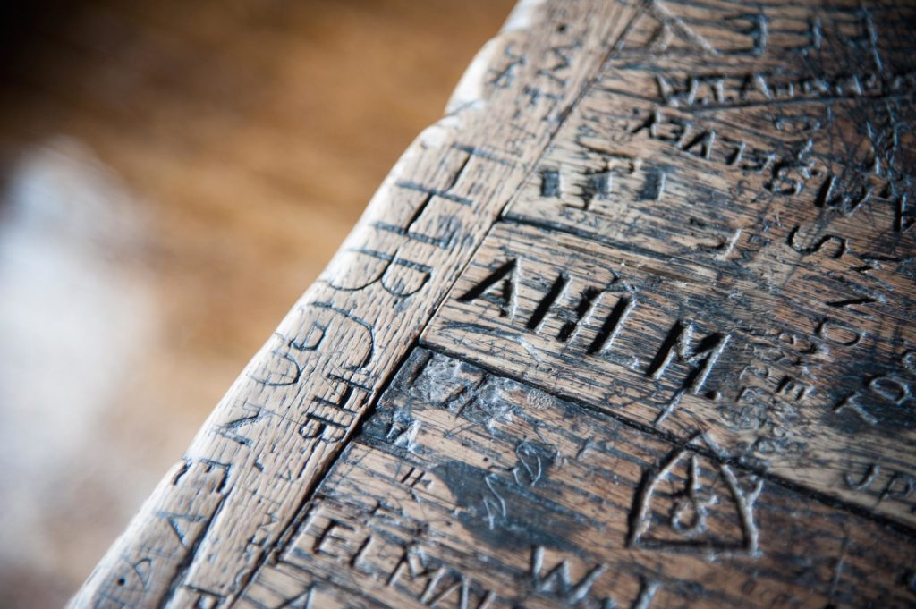 a close photo of a desk with names carved into it