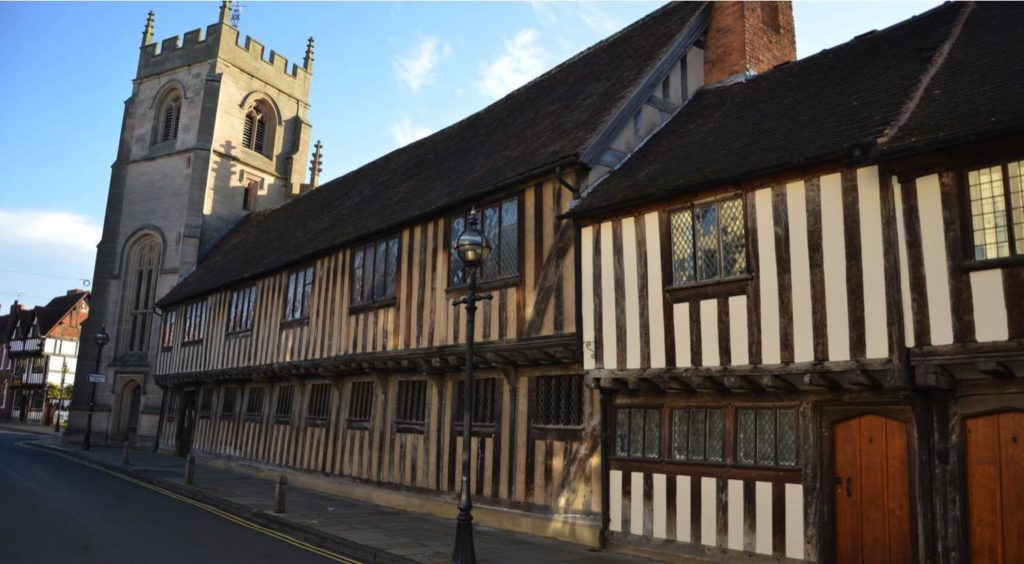 a photo of a Tudor Guildhall type building with church next door