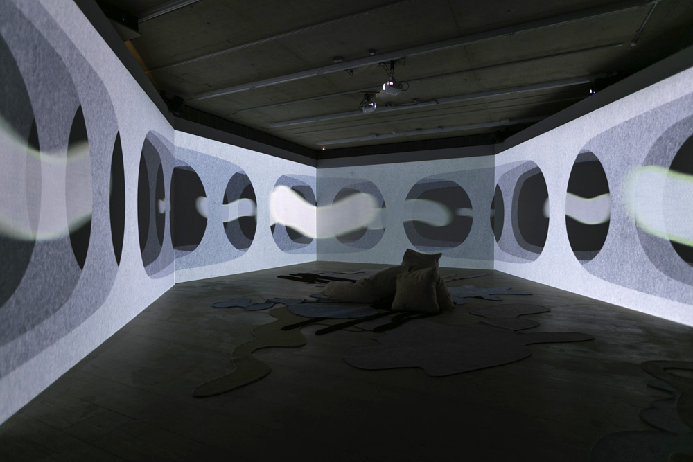 A darkened room with white walls and black circles projected onto them some cushions and carpet arranged on the floor.